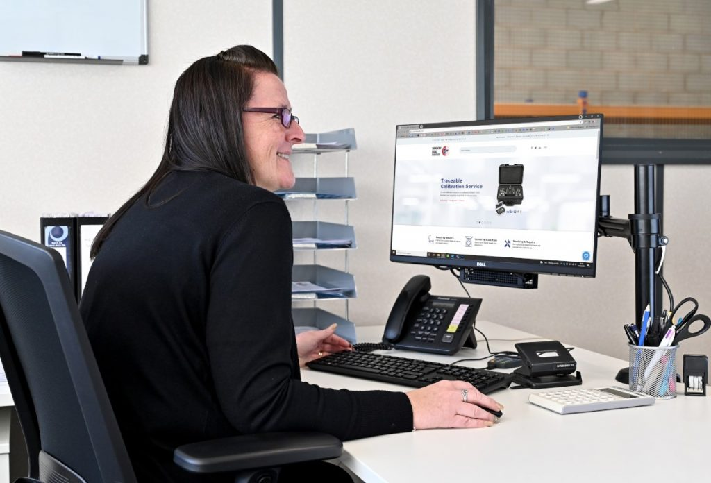 Coventry Scale Company employee sitting at desk happy to take your call. Please contact us.